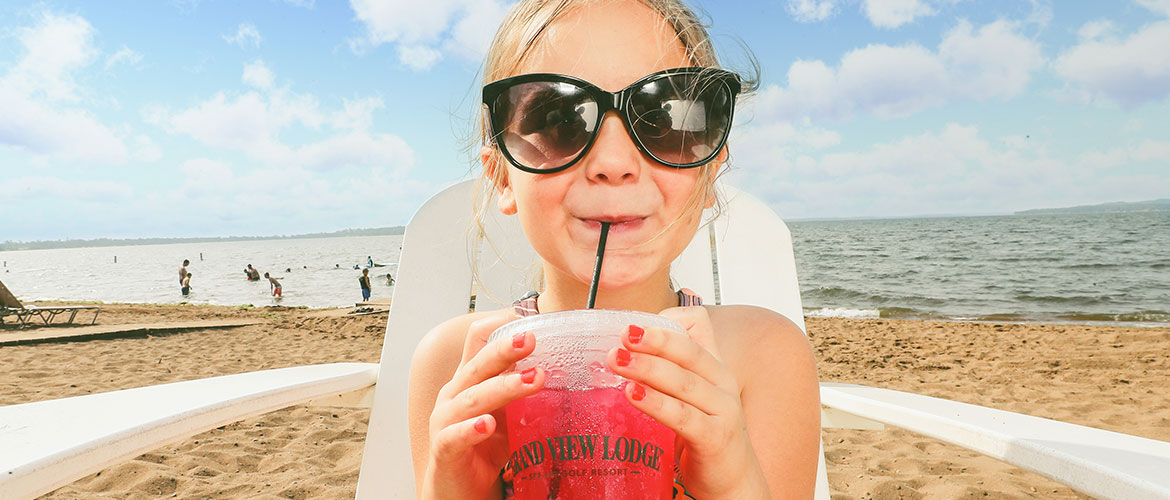 Girl with Kiddie Drink on Beach
